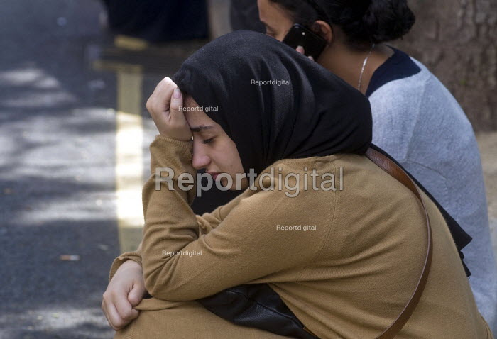 Grenfell Tower Fire. Young woman deeply upset and almost in tears waiting opposite the makeshift evacuation centre at Rugby Portobello Trust for news of victims of the fire that engulfed the West London tower block overnight - Stefano Cagnoni - 2017-06-14