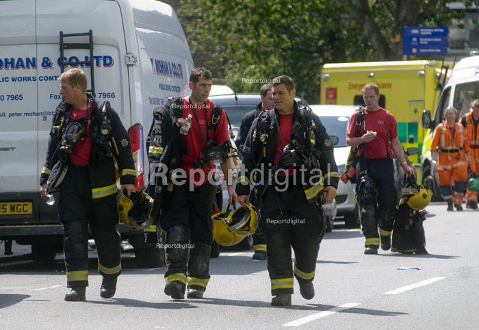 Grenfell Tower Fire. Firefighters in conversation as they leave the site at the end of their shift on the afternoon after the overnight fire at Grenfell Tower which caused the loss of many lives - Stefano Cagnoni - 2017-06-14