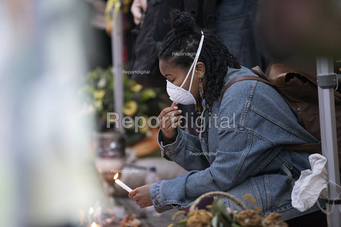 Grenfell Tower fire vigil, one month after the fire, London, woman lights a candle at the Memorial Wall with a mask to protect against feared asbestos - Jess Hurd - 2017-07-12