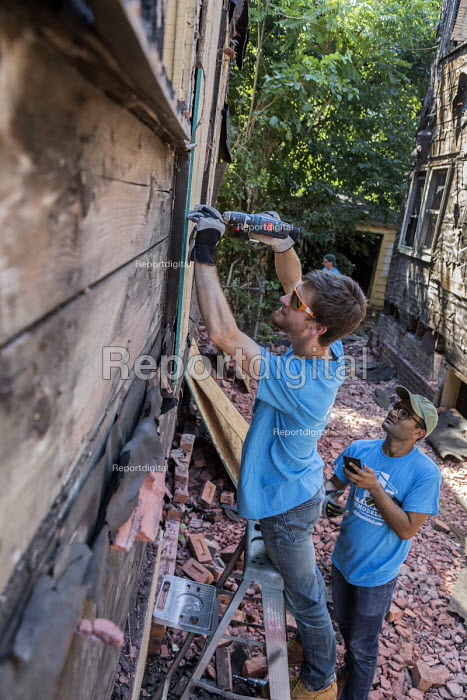 Detroit, Michigan, USA Volunteers in a community improvement project called Life Remodeled workers from Fiat Chrysler Automobiles (FCA) boarding up an abandoned house - Jim West - 2017-08-01