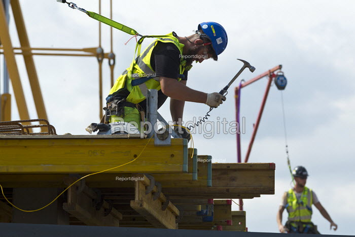 Construction workers with hangman overhead anchor device on a building site, Stratford upon Avon, Warwickshire - John Harris - 2017-08-10