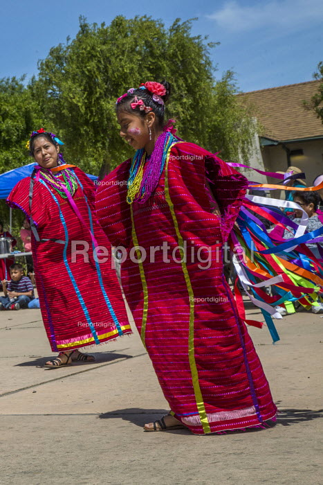 Greenfield, California, USA Migrants from Oaxaca dancing at a festival of Oaxacan indigenous culture in the Salinas Valley where many Triquis have settled. Triqui women from the Mixteca region of Oaxaca in a traditional red Huipiles dance with their children - David Bacon - 2017-04-22