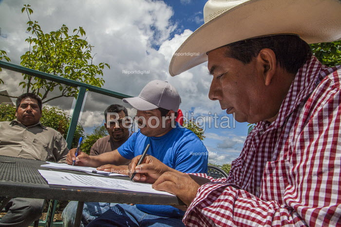 Burlington, Washington, USA Members of Familias Unidas por la Justicia signing a contract negotiated with Sakuma Brothers Farms, with Danny Weeden, general manager of the company, after four years of strikes and boycotts - David Bacon - 2017-06-16
