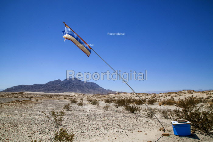 Imperial Valley, California, USA A water station left by a faith group in the desert near the US Mexican border at Mt. Signal. The water point flag is intended to be visible from a distance to help migrants crossing the border from dying of thirst. Hundreds of migrants die each year crossing the border in desert areas - David Bacon - 2017-08-18