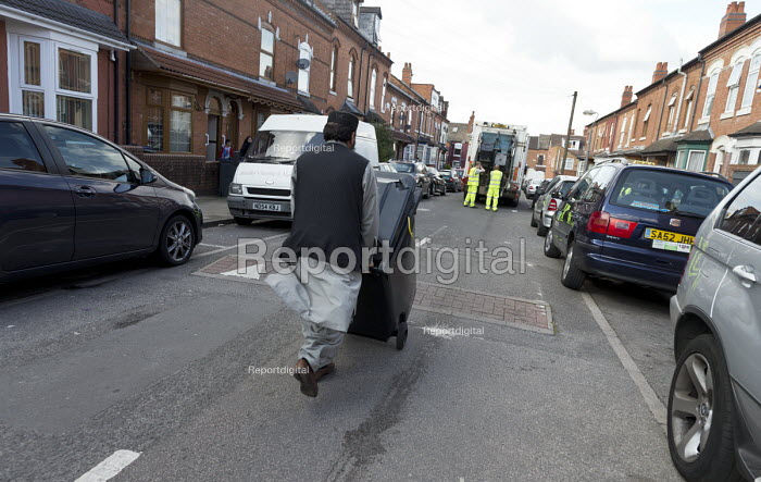 Bin workers strike. Resident pursuing refuse collection by contractors with his wheelie bin, Sparkbrook, Birmingham. Strike is costing 40,000 pounds a day. The Labour council have issued redundancies to 113 binmen - John Harris - 2017-09-17