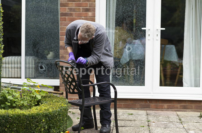 Forensic scene of crime investigator dusting for fingerprints and searching for clues after an attempted break in to a house, Warwickshire. The burglars were disturbed whilst smashing double glazed windows and trying to lever open a door - John Harris - 2017-09-27