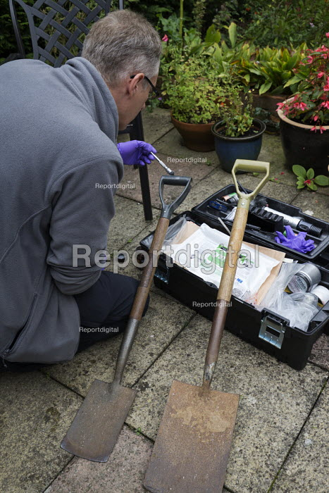 Forensic scene of crime investigator dusting for fingerprints and searching for clues after an attempted break in to a house, Warwickshire. Dusting for prints on the handle of a spade used to try and lever open a locked back door - John Harris - 2017-09-27