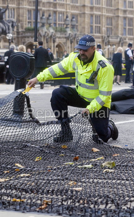 London Police Officers laying out a Talon spiked net outside Parliament to prevent vehicle terror attacks against crowds attending major events. The nets are capable of stopping lorries weighing up to 17 tonnes by puncturing tyres and becoming tangled around the front wheels bringing the vehicle to a stop. The system is designed to ensure that the vehicle skids in a straight line significantly reducing risk to crowds and producing a well controlled stop. The nets can be deployed by two officers in less than a minute - Stefano Cagnoni - 2017-10-02