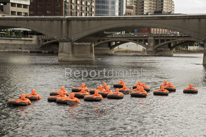Grand Rapids, Michigan USA ArtPrize competition Safety Orange Swimmers by Ann Hirsch and Jeremy Angier displayed in the Grand River. Each of the 22 figures represents more than one million of the 22.5 million refugees estimated to be in the world today - Jim West - 2017-10-05