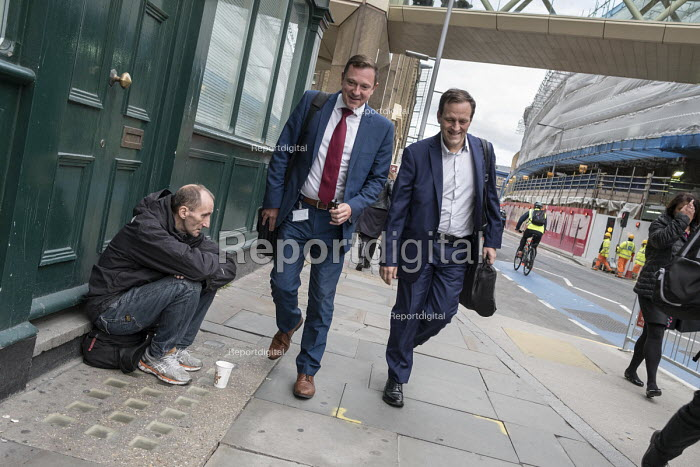 Office workers walking past a homeless man begging in the street, London Bridge business district - Philip Wolmuth - 2017-10-04