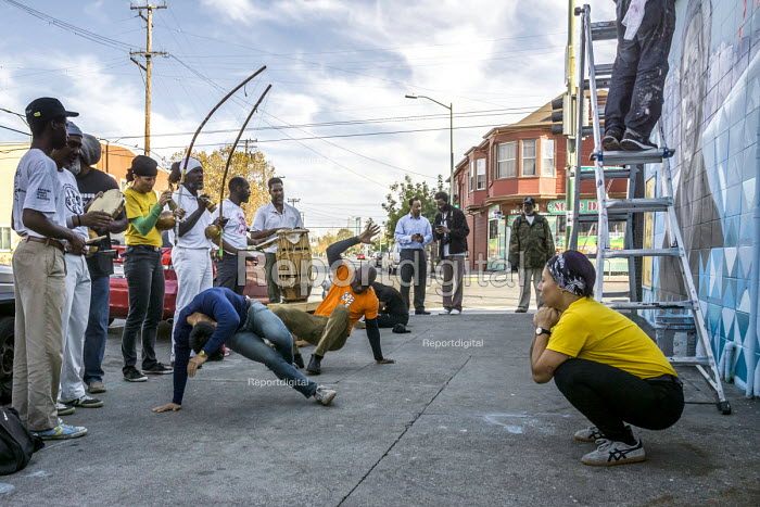 Oakland, California, USA, local capoeira group performing on the sidewalk while artists paint a Black Panther Mural on the wall of a liquor store, celebrating the history of the Black Panther Party. The mural is a portrait of Huey P. Newton, party chairman and an African American couple using food distribution and the party symbol - David Bacon - 2017-10-23