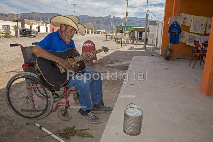 Boquillas del Carmen, Coahuila, Mexico A man in a wheelchair playing a guitar for tips from tourists. The small border town is popular with tourists who cross the Rio Grande from Big Bend National Park. - Jim West - 2017-11-05