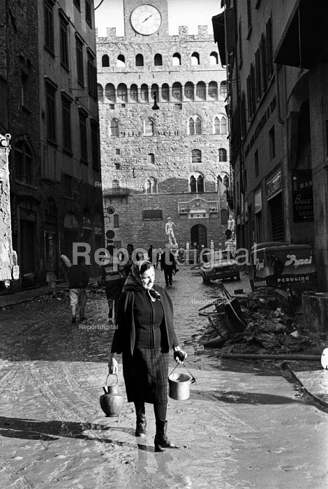 Woman in the street, Florence Floods, Italy, 1966. The floods in Florence in early November 1966 were the worst in over five hundred years and resulted in the loss of over 100 Florentine lives as well as damage to thousands of cultural artefacts, including ancients books, paintings and sculptures. Florentines walking through mud filled streets with pots and pans near the Palazzo Vecchio. - Romano Cagnoni - 1966-11-14