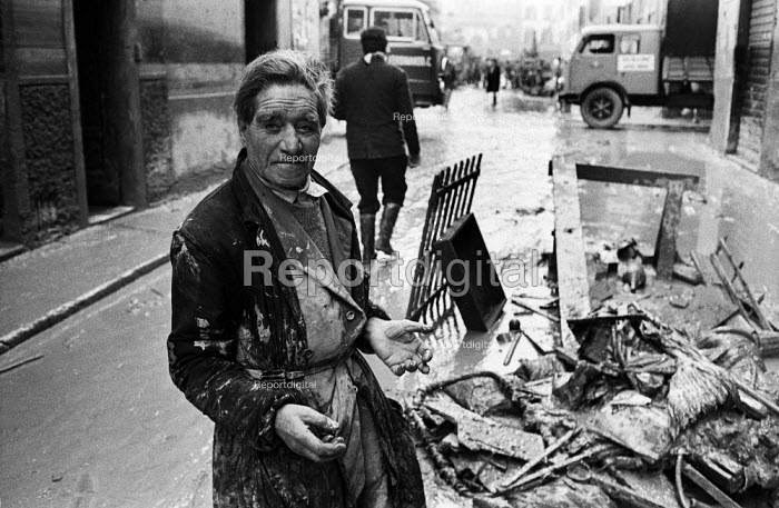 Clearing up, Florence Floods, Italy, 1966. The floods in Florence in early November 1966 were the worst in over five hundred years and resulted in the loss of over 100 Florentine lives as well as damage to thousands of cultural artefacts, including ancients books, paintings and sculptures. Older Florentine man with clothes and hands caked in the mud from the streets of his City - Romano Cagnoni - 1966-11-14