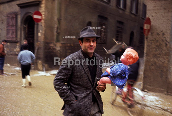 Man with toy doll, Florence Floods, Italy, 1966. The floods in Florence in early November, 1966, were the worst in over five hundred years and resulted in the loss of over 100 Florentine lives as well as damage to thousands of cultural artefacts, including ancients books, paintings and sculptures. Florentine man in hat carrying a childs doll through the mud filled streets of his City - Romano Cagnoni - 1966-11-14