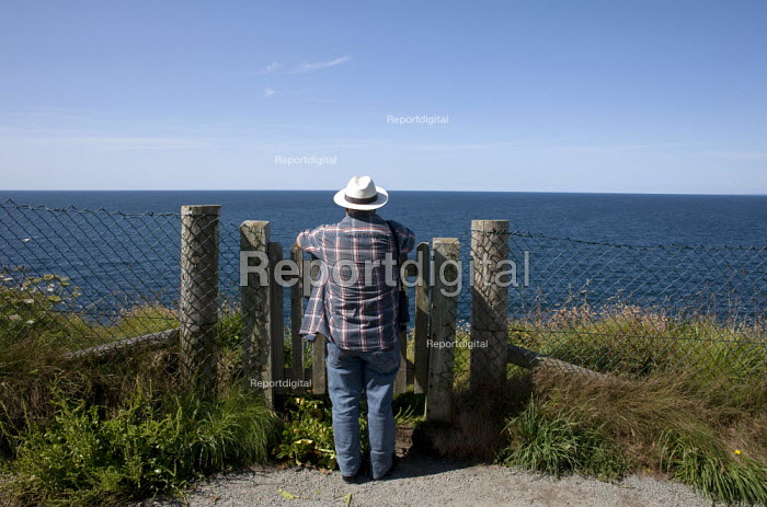 Port Issac, Cornwall Tourist admiring the spectacular view of the sea. A gate gives access through a safety fence on the cliff top - David Mansell - 2015-07-15