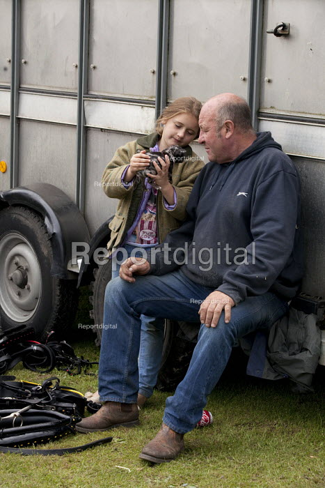 Horsmonden Gypsy Horse Fair, Kent. Father and daughter looking at one of the puppies they hope to sell. This Charter Fair dates back over 400 years and is held on the second Sunday in September and in recent times it became an important event for the people picking hops as it became known as Hoppers Fair. - David Mansell - 2015-09-13
