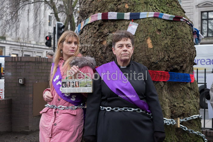 Vicar chained to tree in HS2 Euston protest. Local resident Jo Hurtfurd and Rev Anne Stevens, Vicar of St Pancras, chained to one of more than 200 mature trees before felling begins to make way for HS2 construction trucks at Euston station, London - Philip Wolmuth - 2018-01-12