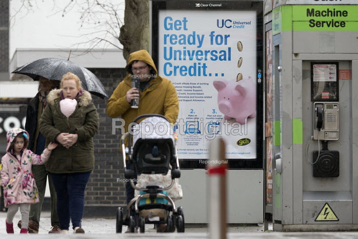 Pedestrians walking past a Get Ready For Universal Credit advertisment, Gloucester city centre. Coins dropping into a piggy bank - John Harris - 2018-02-03