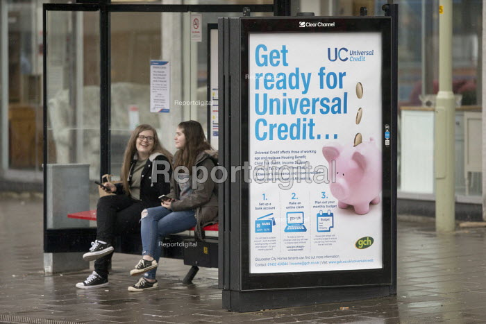 Passengers waiting at a bus stop with a Get Ready For Universal Credit advertisment, Gloucester city center. Coins dropping into a piggy bank - John Harris - 2018-02-03