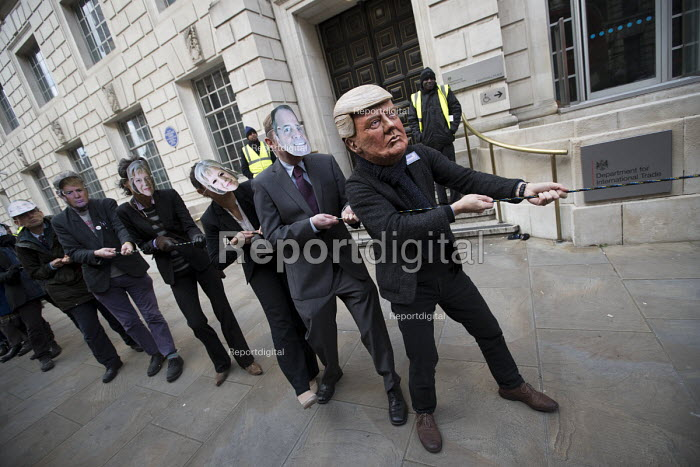 Symbolic tug of war with Donald Trump, Theresa May and other leaders highlighting issues of trade democracy outside the Department for International Trade, organised by War on Want and Global Justice Now, London. - Jess Hurd - 2018-02-06