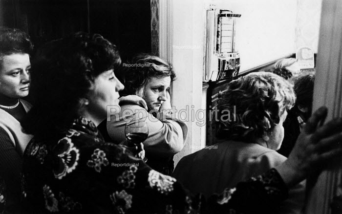Women workers watching from outside the door as men discuss closure of Adelphi Mill, Bollington, Cheshire, 1975. The women later joined in the discussion - John Sturrock - 1975-11-29