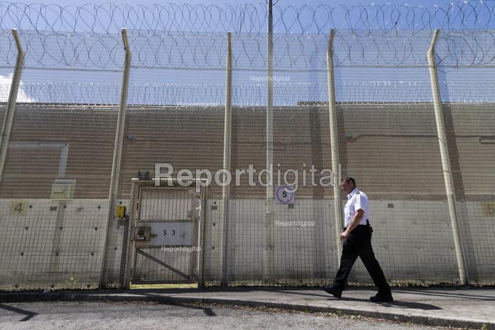 Prison officer walking past razor wire security fence, Bristol HMP - John Harris - 2017-06-15
