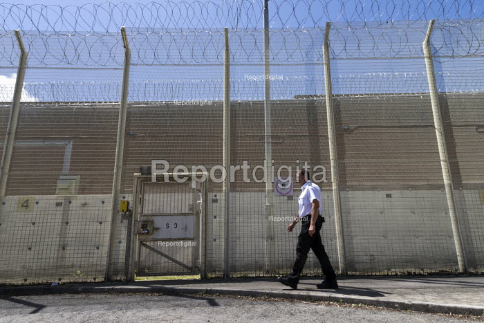 Prison officer walking past razor wire security fence, Bristol HMP - John Harris - 2017-06-15