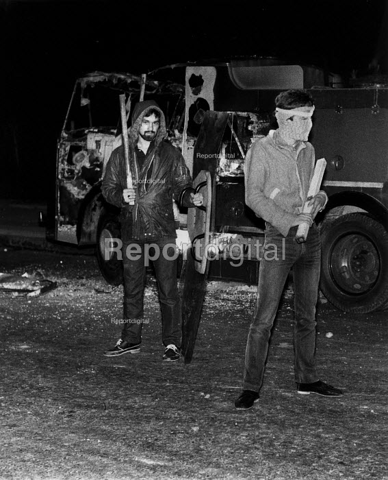 Toxteth riots, Liverpool 1981 Rioters pose with a police shield and baton in front of a burnt out fire engine - John Harris - 1981-07-06