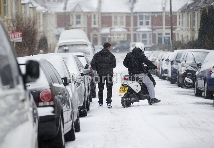 Youth driving motor scooter on the snow covered streets of Bristol. - Paul Box - 2018-03-01