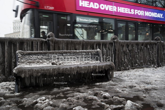 Filthy, frozen bench seat due to a burst water main, Globe Town, East London. A bus passing. - Jess Hurd - 2018-03-03