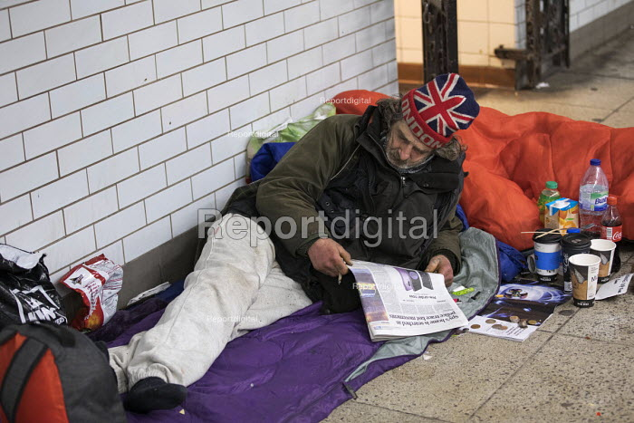 Homeless man with Union Jack London hat, Westminster, London. Reading a story in the Evening Standard newspaper - Jess Hurd - 2018-03-09