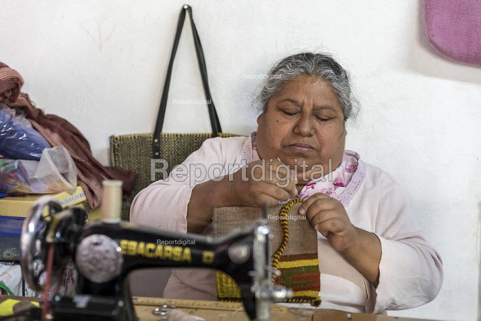 Teotitlan del Valle, Oaxaca, Mexico, woman stitching handbags at her home in a small Zapotec village. Microfinance loans from the non profit En Via are supporting small businesses in the village - Jim West - 2018-02-24