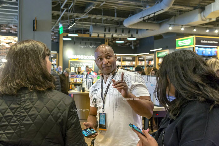 Georgetown, Washington DC Amazon bookshop that has replaced a Barnes & Noble bookstore. It displays 5,600 titles that are highly rated on the Amazon.com website Assistant store manager John Shorter showing customers how to check a book price with an app on their mobile phone - Jim West - 2018-03-25