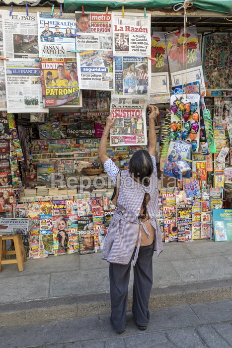 Oaxaca, Mexico Newsstand worker adding a newspaper to the display - Jim West - 2018-02-20