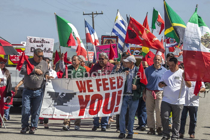 California, USA Migrant farm workers and their supporters march in protest at immigration raids. Organized by the UFW union, also celebrating the birthday of union founder Cesar Chavez. UFW President Arturo Rodriguez at the front of the march. We Feed You banner - David Bacon - 2018-04-08