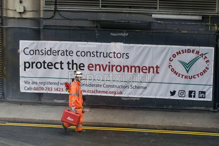 Construction worker carrying Leica Builder 100 Theodolite equipment on building site, Waterloo London. Considerate constructors protect the environment banner - Stefano Cagnoni - 2018-03-20