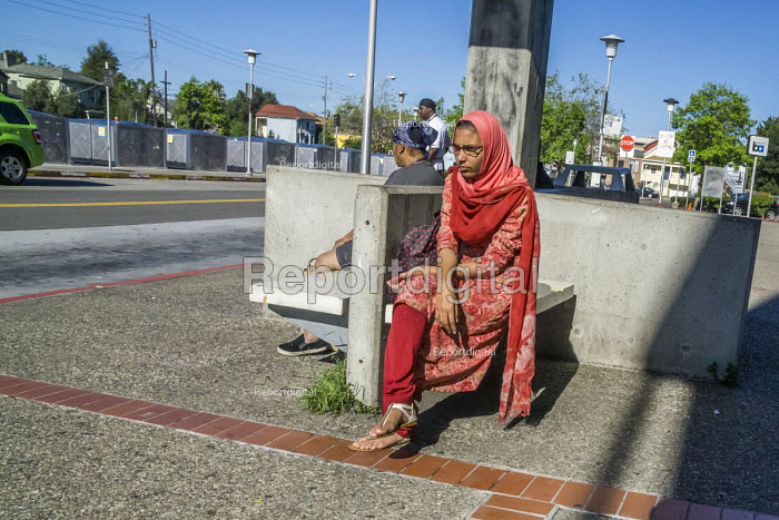 Oakland, California, USA: Asian woman waiting for a bus connection to the Bay Area Rapid Transit - David Bacon - 2016-04-16