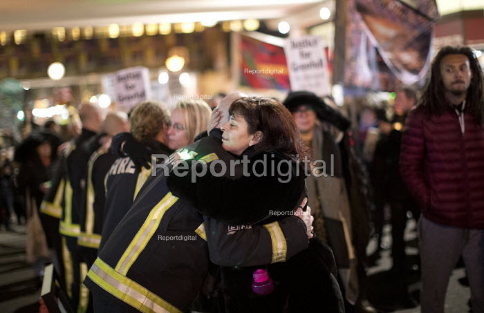 Hugging a firefighter, Justice for Grenfell six month anniversary silent walk, Kensington and Chelsea, London - Jess Hurd - 2017-12-14