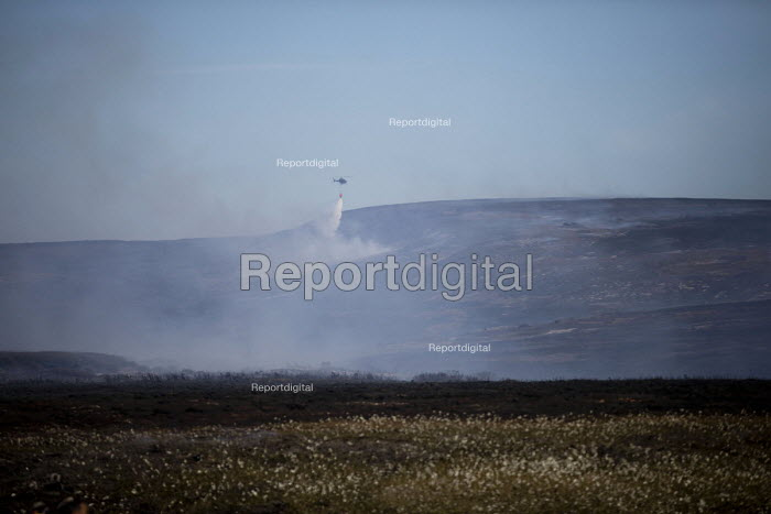 Helicopter dropping water onto Saddleworth Moor fire, Stalybridge, Derbyshire. Provided by water firm United Utilities it is being used to collect water from a nearby reservoir and drop it on the moorland - Jess Hurd - 2018-06-28
