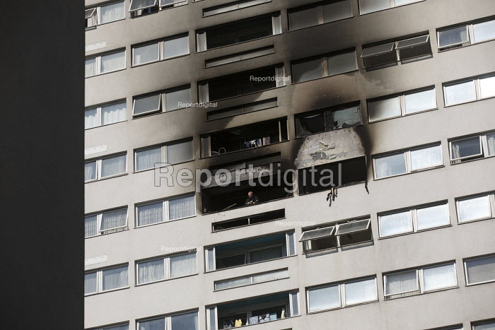Firefighter looks out from a window of Grafton House where a twelfth floor fire is contained and brought under control by over 50 firefighters at a 22 story East End Homes tower block in Mile End, East London - Jess Hurd - 2018-06-29