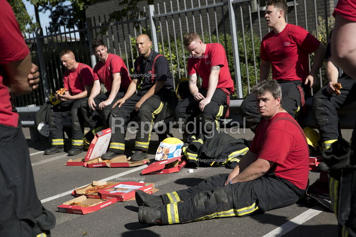 Exhausted firefighters from White Watch taking a break with gifted Domino's pizza as Grafton House twelfth floor fire is contained and brought under control by over 50 firefighters at a 22 story East End Homes tower block, Mile End, East London - Jess Hurd - 2018-06-29