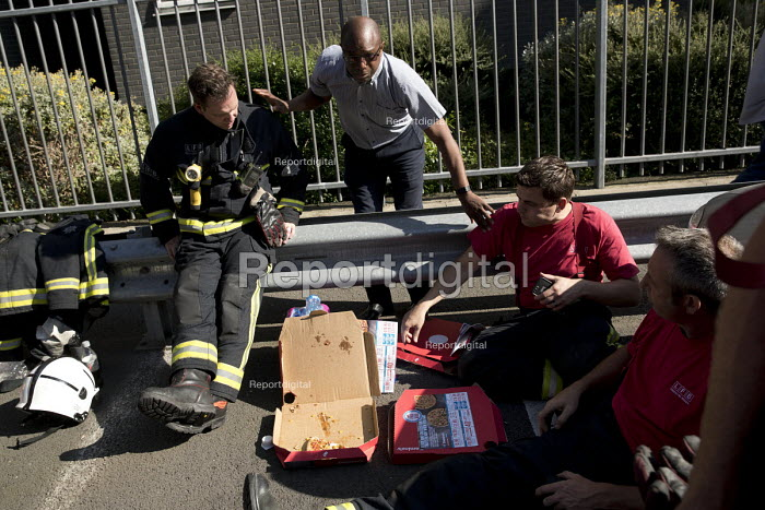 Local resident thanks exhausted firefighters from White Watch taking a break with gifted Domino's pizza as Grafton House twelfth floor fire is contained and brought under control by over 50 firefighters at a 22 story East End Homes tower block, Mile End, East London - Jess Hurd - 2018-06-29
