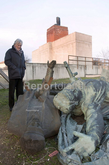 Visitor looking at disgarded Soviet era statues, including one of Lenin, laying outside Memento Park Museum Budapest, Hungary - Janina Struk - 2014-01-02