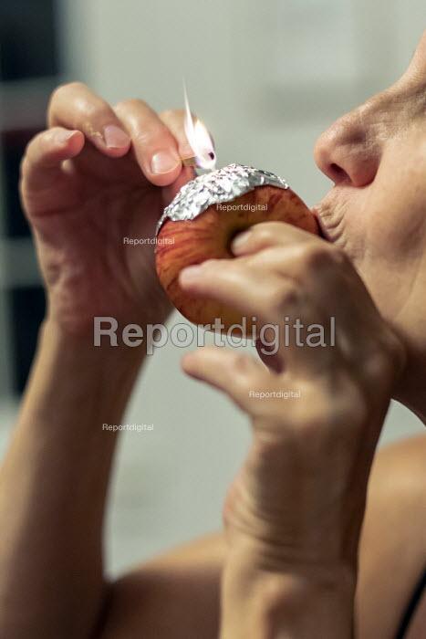 Woman smoking marijuana using an apple as a pipe - Jim West - 2018-07-24