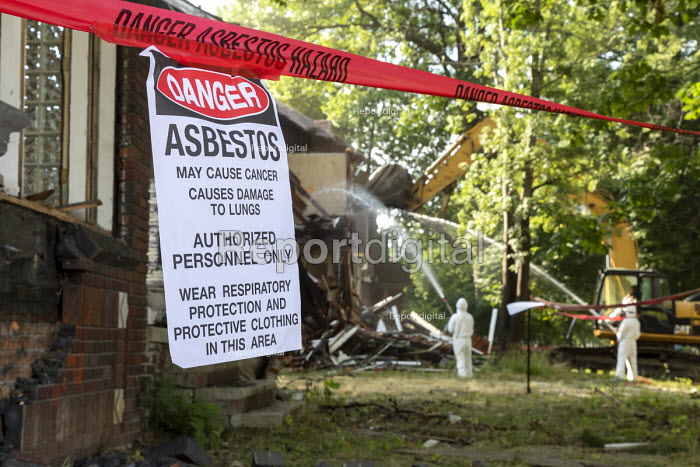 Detroit, Michigan, USA Sign warning about asbestos exposure. Workers demolishing an abandoned house wearing protective clothing against asbestos exposure. They are spraying water onto the building to keep asbestos from becoming airborne - Jim West - 2018-07-30
