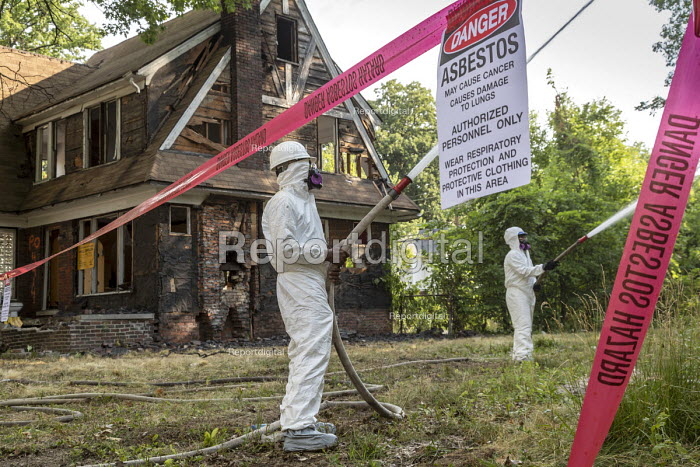Detroit, Michigan, USA workers demolishing an abandoned house wearing protective clothing against asbestos exposure. They are spraying water onto the building to keep asbestos from becoming airborne - Jim West - 2018-07-30