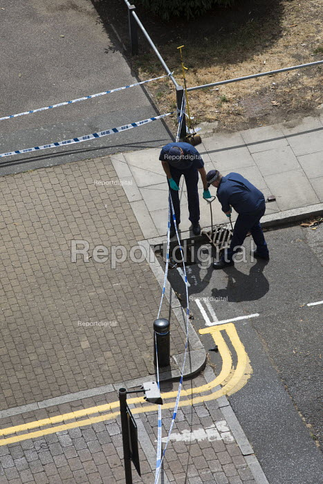 Police forensic team searching the drains with a large magnet after a stabbing of a teenager, Knapp Road, East London - Jess Hurd - 2018-08-04