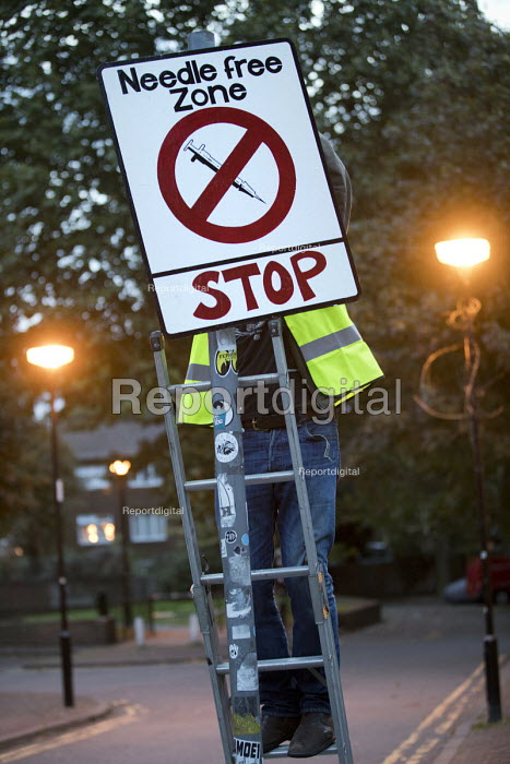 Community activists erecting spoof street signs highlighting the levels of drug dealing in London E2, which apparently has the cheapest heroin in Europe. The anti drugs street art campaign called the Columbia Road Cartel has been commissioned by the Weavers Community Action Group. Shoreditch, East London. Needle free zone stop sign - Jess Hurd - 2018-09-16