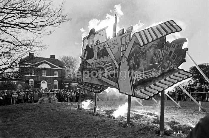 Protest against new third London airport, Hoggeston village, Buckinghamshire, 1979. An effergy of a bulldozer consuming rual communities being burnt. The campaign to oppose the proposal was headed by Wing Airport Resistance Association (WARA), led by Desmond Fennell, a barrister living in Winslow, and Bill Manning, an Aston Abbotts farmer. At its height, the Association claimed 61,000 signed-up members and raised £50,000 (nearly £300,000 at to-day's prices), with activities co-ordinated from an office in Leighton Buzzard. It was later acknowledged as the first major campaign for the environment. - Martin Mayer - 1979-12-16